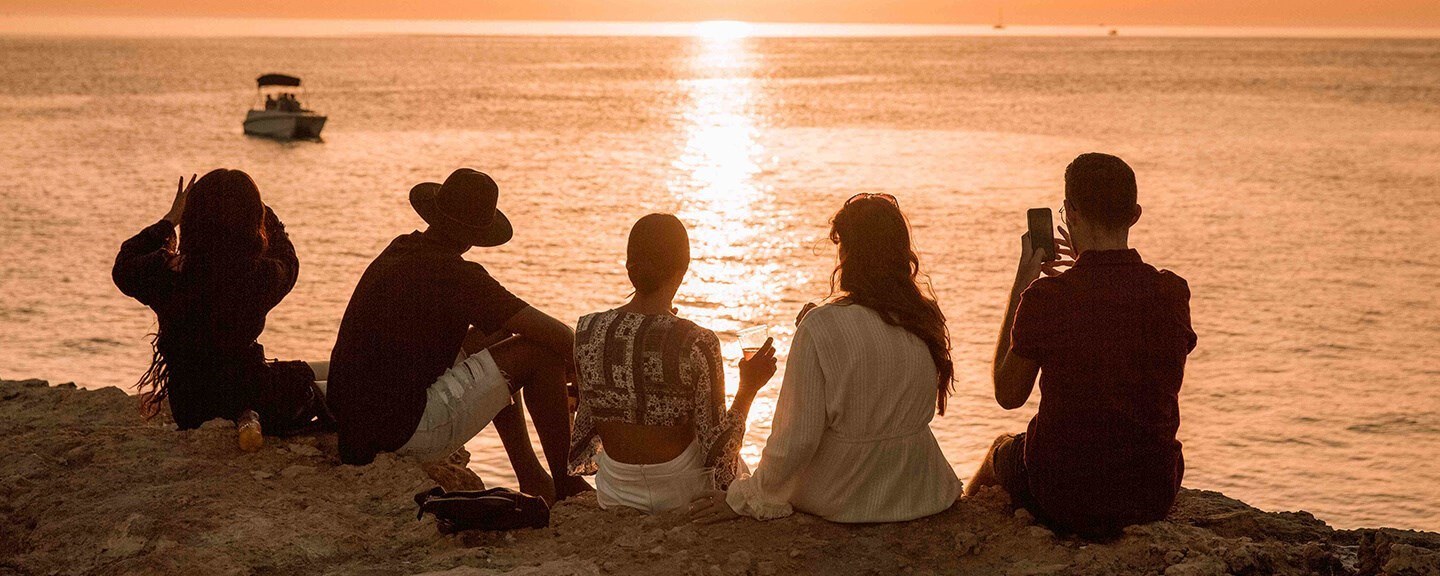 Group of trverlers watching the sunset at the beach.